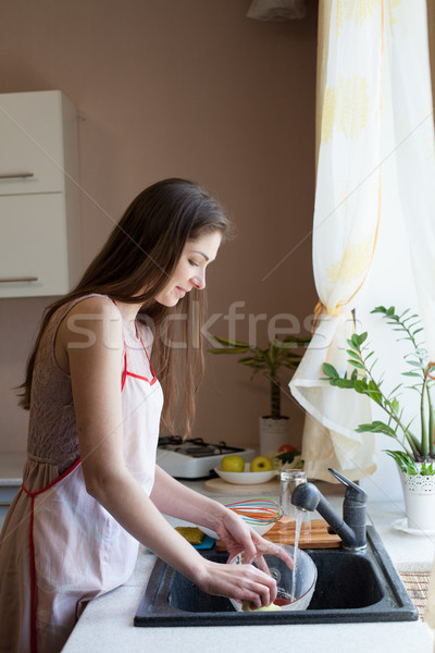 girl housewife washes dirty dishes in the kitchen Stock photo © dmitriisimakov