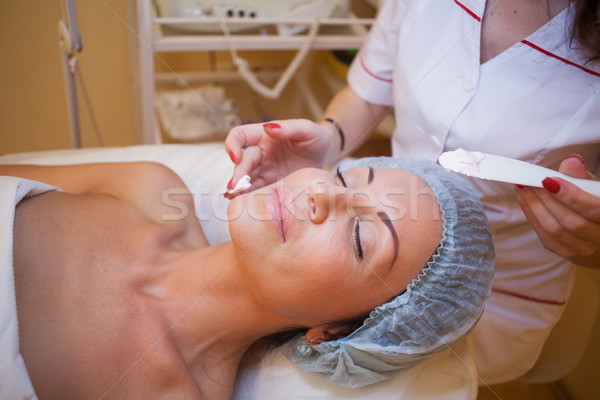 Cosmetology doctor makes woman treatments facial massage Stock photo © dmitriisimakov