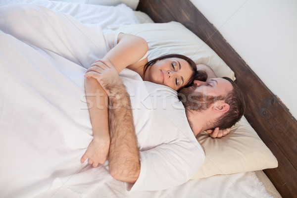 a man and a woman sleeping in a bedroom in white bed Stock photo © dmitriisimakov