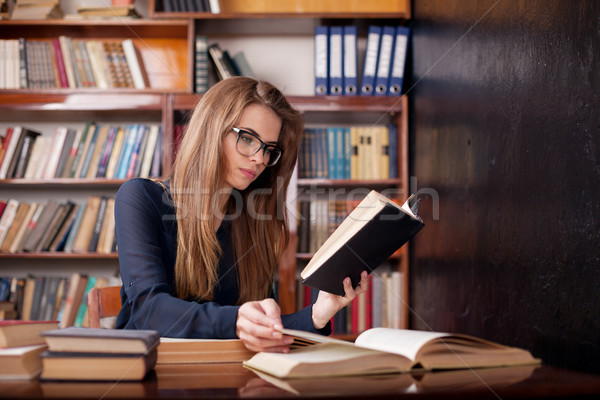 girl student sits in the library reading Stock photo © dmitriisimakov