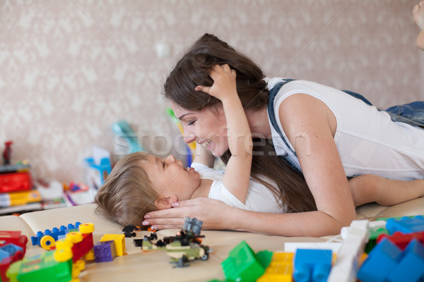 mom plays with a little boy with love kisses laughs Stock photo © dmitriisimakov