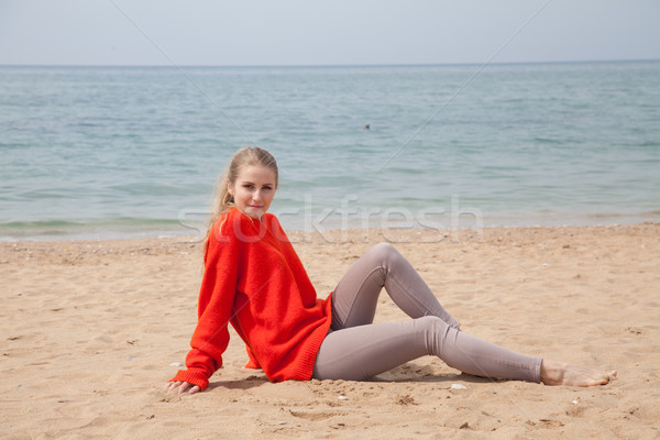the blonde in the red walks along the beach of the sea coast Stock photo © dmitriisimakov