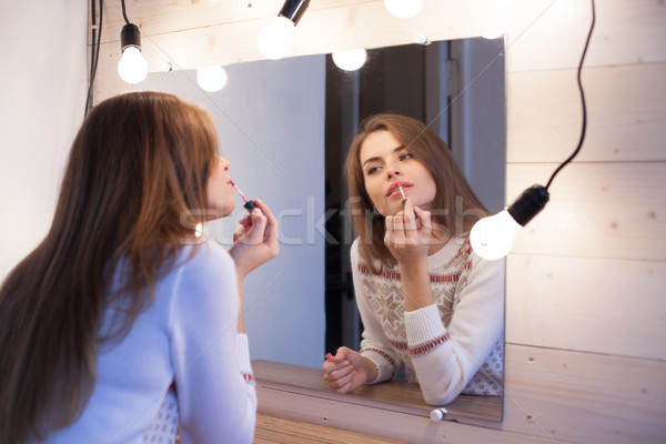 beautiful girl stands before the mirror and makes makeup Stock photo © dmitriisimakov