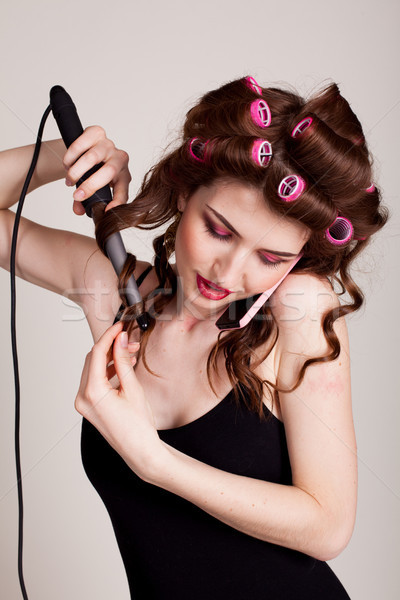 girl with hair curlers talking on the phone and makes the hairstyle Stock photo © dmitriisimakov