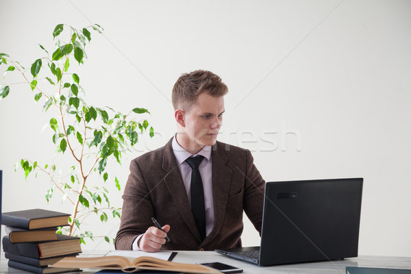 Stock photo: a man in a business suit works at a desk with a computer and books in the Office