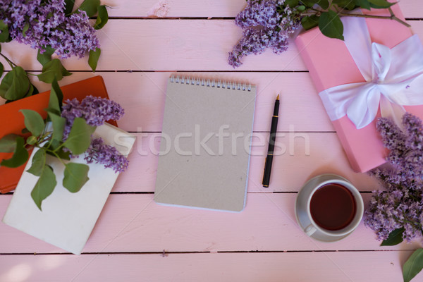 on the white table lilac, gift, notebook, cup of tea Stock photo © dmitriisimakov