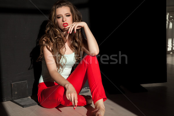 Portrait of fashionable girl in red pants on a black background Stock photo © dmitriisimakov