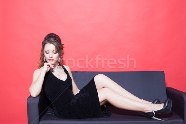 beautiful girl in black evening dress sitting in the red room on the couch Stock photo © dmitriisimakov