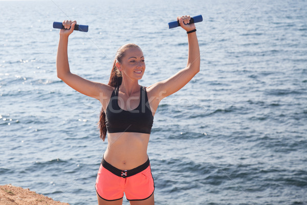 Fitness Sports girl trains muscles with dumbbells Stock photo © dmitriisimakov