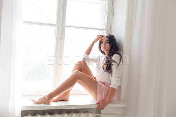girl sits at a window in a white room Stock photo © dmitriisimakov