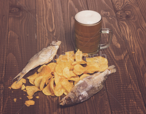 Fishes with frothy beer next to  diffuse chips on the wood table Stock photo © dmitroza