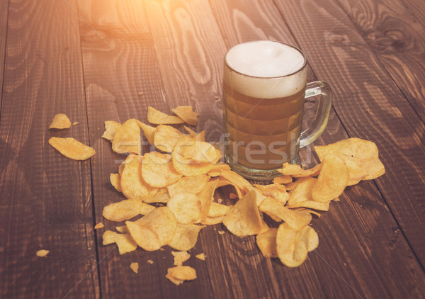 Frothy beer and chips Stock photo © dmitroza