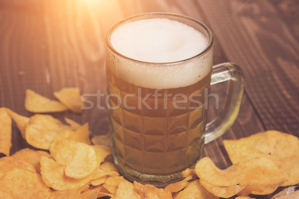 Frothy beer and crunchy chips Stock photo © dmitroza