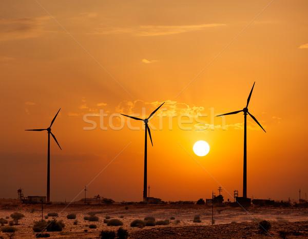 Wind generator turbines sihouettes on sunset Stock photo © dmitry_rukhlenko