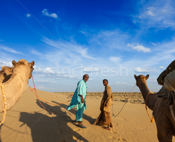 Two cameleers (camel drivers) with camels in dunes of Thar deser Stock photo © dmitry_rukhlenko