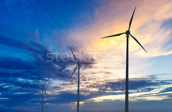 Stock photo: Wind generator turbines sihouettes on sunset