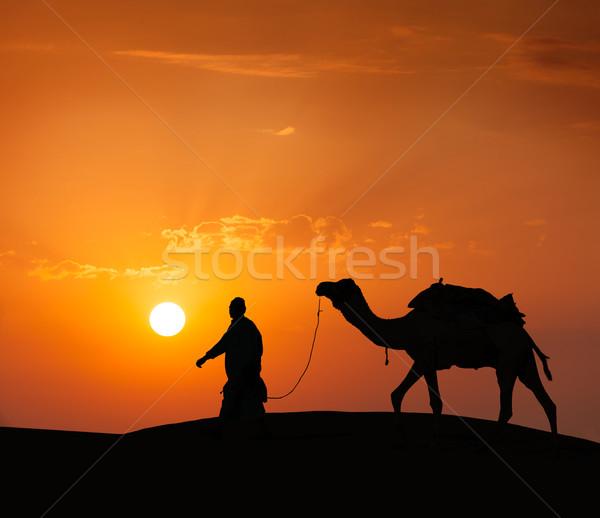 Cameleer (camel driver) with camels in dunes of Thar desert. Raj Stock photo © dmitry_rukhlenko