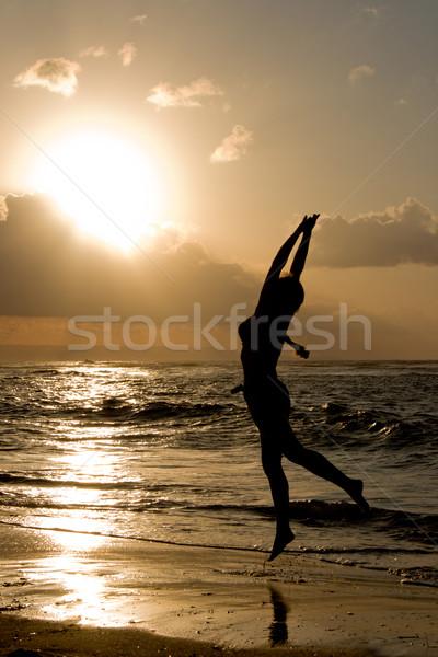 Menina saltando nascer do sol praia pôr do sol mar Foto stock © dmitry_rukhlenko