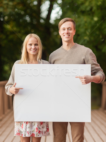 romantic couple with blank white board Stock photo © dolgachov