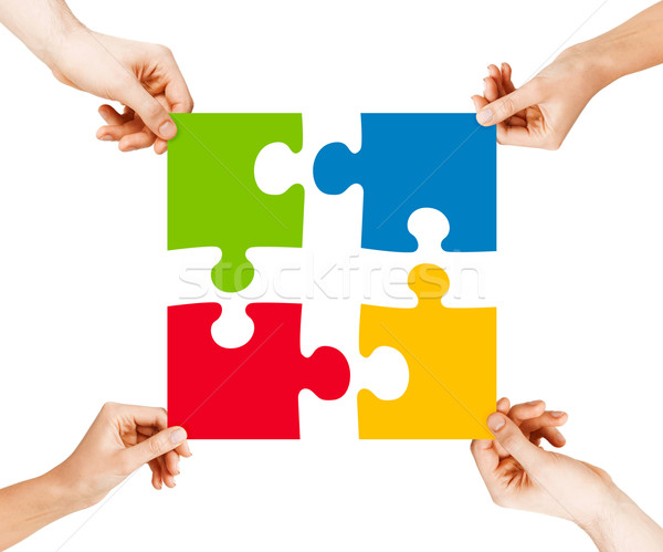 four hands connecting puzzle pieces Stock photo © dolgachov