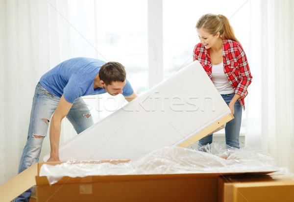 smiling couple opening big cardboard box with sofa Stock photo © dolgachov