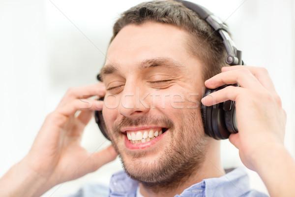 улыбаясь молодым человеком наушники домой технологий музыку Сток-фото © dolgachov