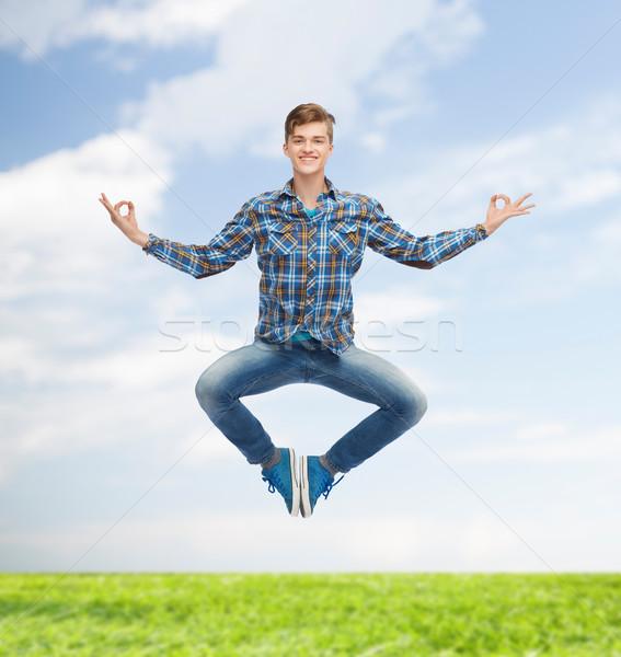 smiling young man jumping in air Stock photo © dolgachov
