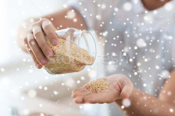 close up of male emptying jar with quinoa Stock photo © dolgachov