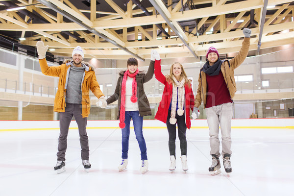happy friends waving hands on skating rink Stock photo © dolgachov