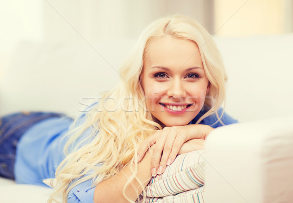 Stock photo: smiling young woman lying on sofa at home