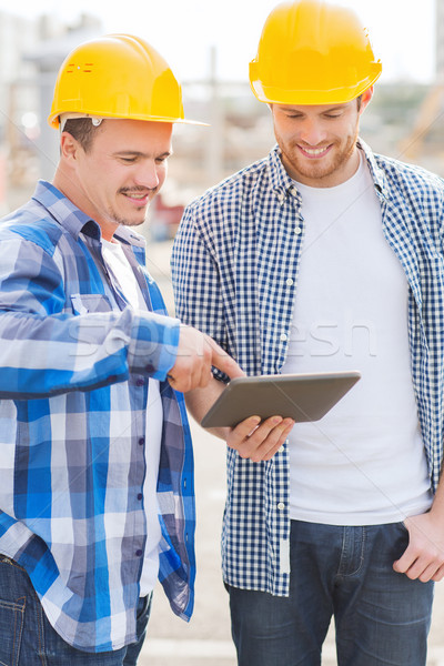 smiling builders with tablet pc outdoors Stock photo © dolgachov
