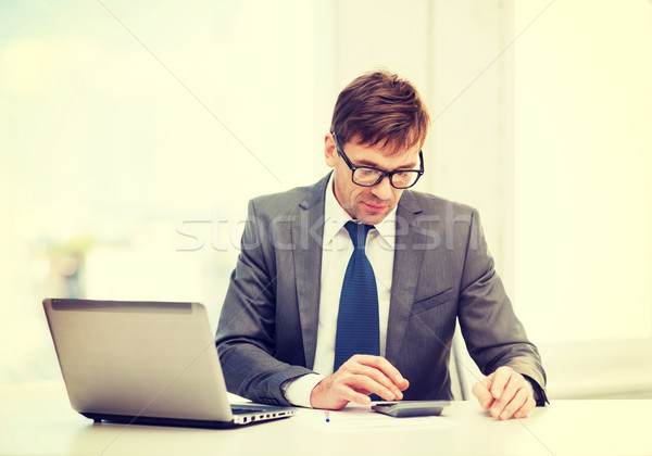 businessman with computer, papers and calculator Stock photo © dolgachov