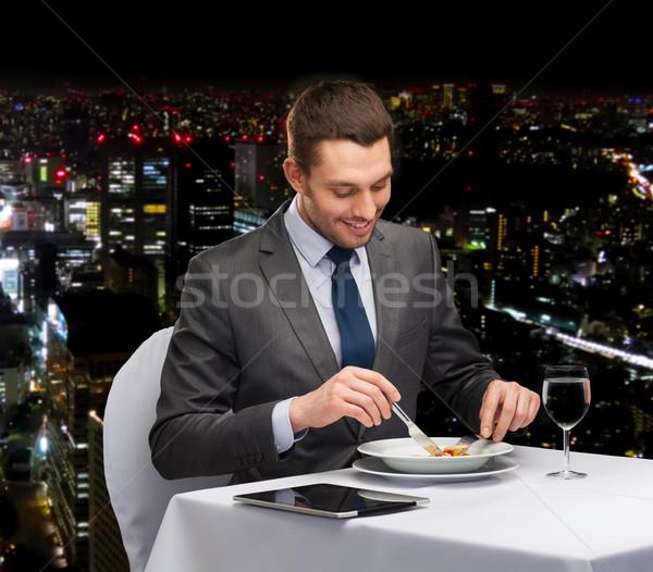 Uśmiechnięty człowiek jedzenie danie główne restauracji Zdjęcia stock © dolgachov