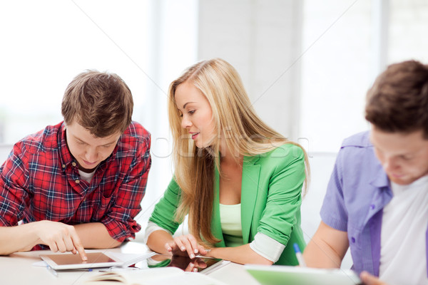 Stock photo: students browsing in tablet pc at school