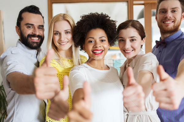 happy creative team showing thumbs up in office Stock photo © dolgachov