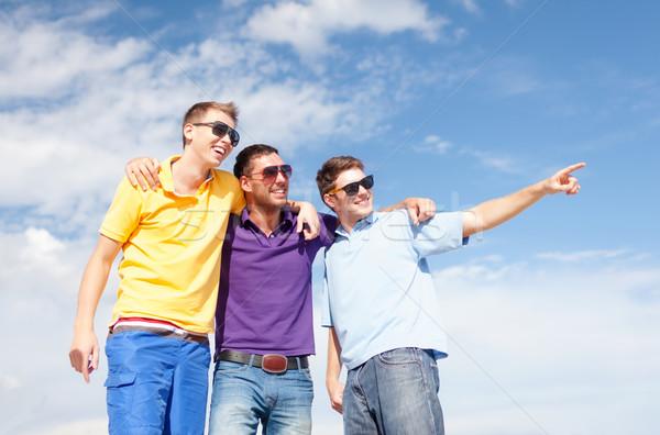 smiling friends in sunglasses pointing finger Stock photo © dolgachov