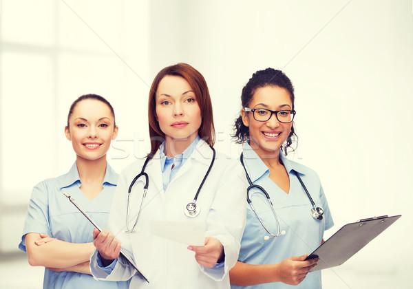 calm female doctor with clipboard Stock photo © dolgachov