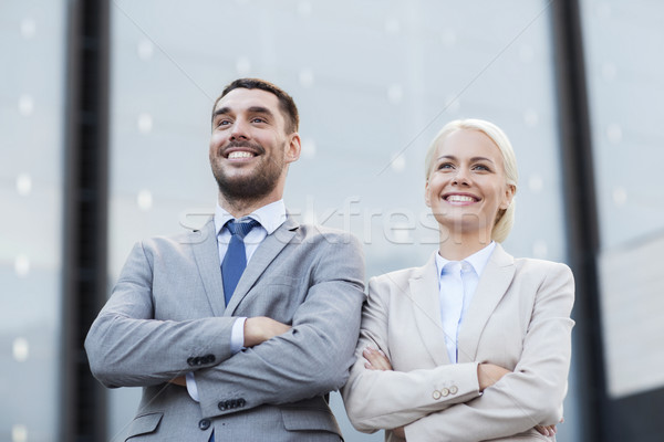 Stock photo: smiling businessmen standing over office building
