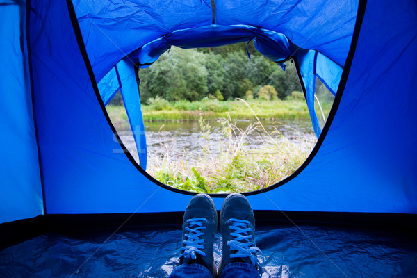 close up of camper legs lying near tent entrance Stock photo © dolgachov