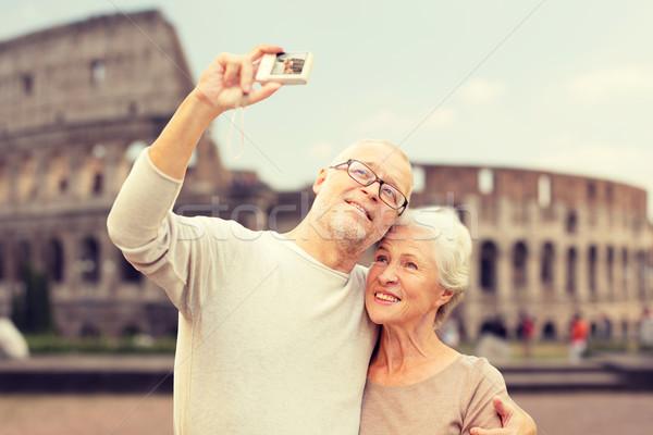 senior couple photographing over coliseum Stock photo © dolgachov