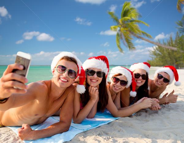 Csoport barátok mikulás sapkák okostelefon nyári vakáció Stock fotó © dolgachov