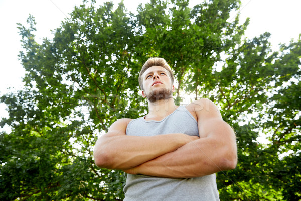 sporty young man with crossed arms at summer park Stock photo © dolgachov