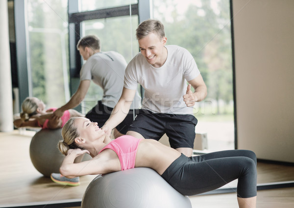 smiling young woman with personal trainer in gym Stock photo © dolgachov