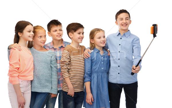 happy children with smartphone and selfie stick Stock photo © dolgachov