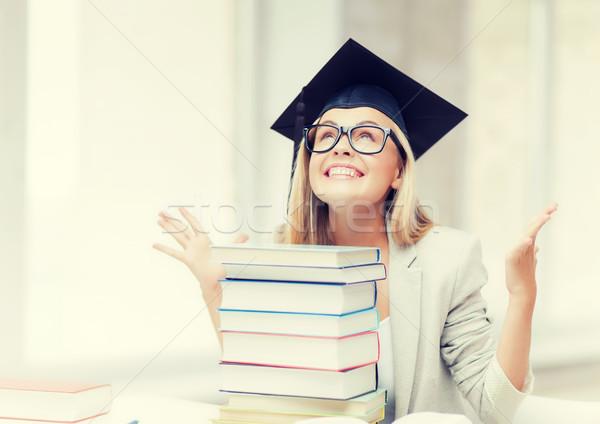 Boldog diák érettségi sapka boglya könyvek Stock fotó © dolgachov