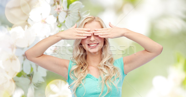 smiling young woman or teen girl covering her eyes Stock photo © dolgachov