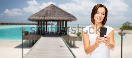 smiling young woman taking selfie with smartphone Stock photo © dolgachov