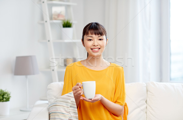 Stock photo: happy asian woman drinking from tea cup