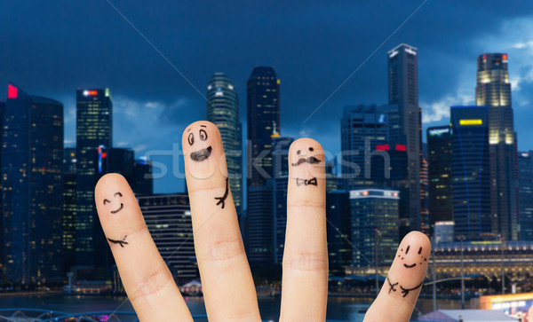 close up of fingers with smiley faces over city Stock photo © dolgachov