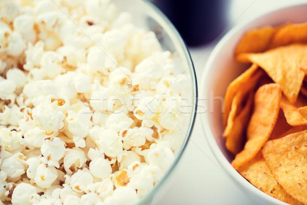 close up of popcorn and corn crisps or nachos Stock photo © dolgachov